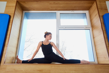 Woman on the splits in the window at the gym. Gymnastics, yoga, relaxation.