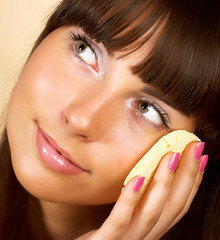 Portrait of young happy smiling beautiful woman applying creme