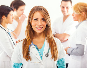 Attractive female doctor portrait and group of her fellow workers in background.