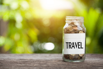 TRAVEL word with coin in glass jar with Savings and financial investment concept.