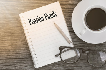 Concept Pension Funds message on notebook with glasses, pencil and coffee cup on wooden table.