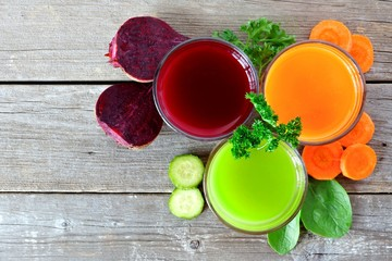 Three glasses of healthy vegetable juice with surrounding ingredients, above view over rustic wood