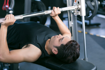 Man lifting dumbbell weights while lying down in gym.