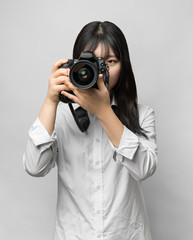 Asian woman holding DSLR camera