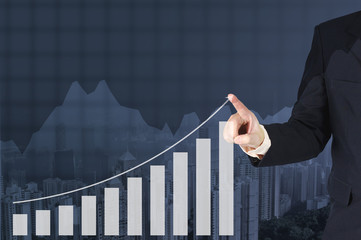 Double exposure businessman hand touching virtual panel of growth bar chart on financial graph chart and building background.