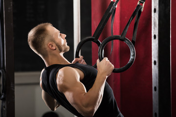 Fitness Man Pulling Up On Gymnastic Rings