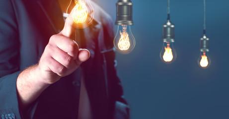 Mann zeigt mit Finger auf eine Glühbirne
