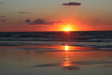 Morning on the atlantic ocean beach. Red sun rising over the ocean. Background with the first rays of the sun rising over the Atlantic Ocean.