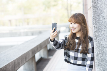 young woman selfie in the park with a smartphone doing v sign