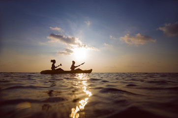 silhouette of people kayaking at sunset