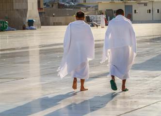Mans muslim pilgrim in white traditional clothes.