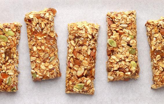 Homemade granola bars on white baking paper.