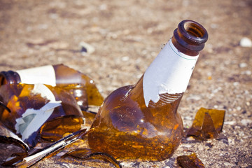 Shattered beer bottle resting on the ground: alcoholism concept - toned image with copy space