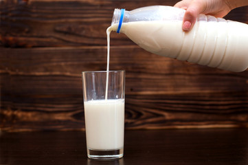 female hand is pouring milk in a glass on a wooden background