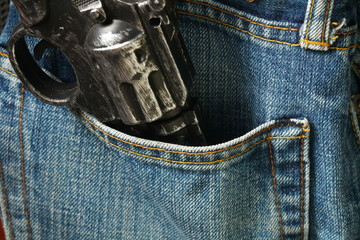 The old and dirty plastic toy gun in the jean pocket represent the crime and weapon concept related idea.
