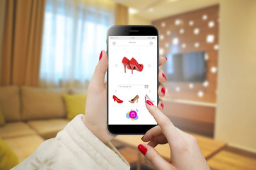 Women searching and ordering shoes online.  Online shopping with smartphone