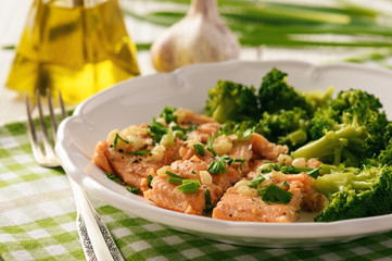 Baked salmon trout served with boiled broccoli.