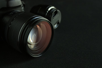 closeup digital camera on black wooden table with soft-focus in the background. dark color tone and over light