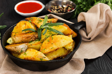 Fried potatoes with fresh rosemary in cast-iron pan