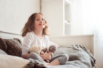 happy kid girl playing with teddy bears in her room, sitting on bed in the morning