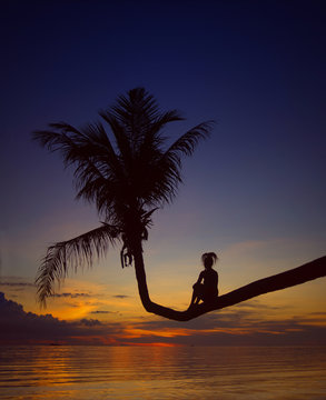 girl on palm tree, silhouette at sunset