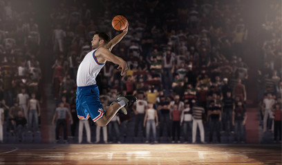basketball player jumping with ball on stadium