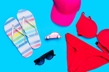 beautiful swimsuit, sunglasses, car shaped toy, cap and sandals on the wonderful blue background