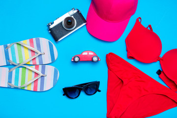 beautiful swimsuit, sunglasses, car shaped toy, camera, cap and sandals on the wonderful blue background