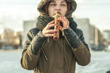 Woman in warm clothing playing a musical instrument flute outdoors on a sunny afternoon outside, holding, fingering, near the mouth