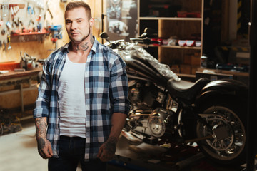 Handsome biker being circled with tools