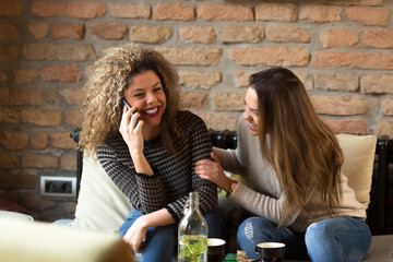 Two girls are smiling and using smart phone in a cafe