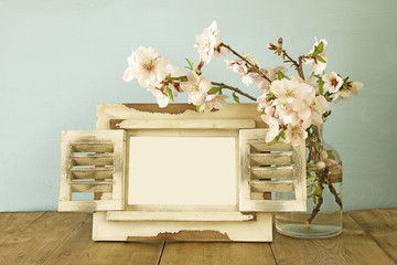 Vintage blank photo frame next to spring flowers