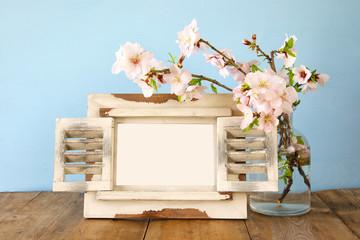 Vintage blank photo frame next to spring flowers