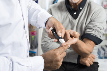 Doctor Checking Sugar Level Of Senior Patient With Glucometer