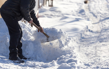 Worker cleans snow shovel