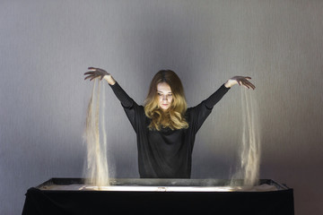 The woman draws on sand, sand animation, sand spilling out of two hands