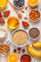 Ingredients for a healthy breakfast -  oatmeal, granola, honey, nuts, berries, fruits