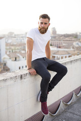Bearded man sitting in the wall.