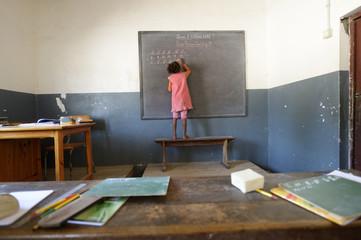 Madagascar, Fianarantsoa, Schoolgirl writing on blackboard