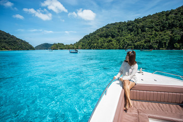 beautiful girl sit on the head speed boat and seeing beautiful sea at Surin island, thailand