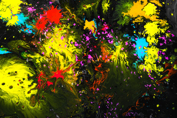 Abstract artistic photograph of a staged action painting scene. Liquid Colors ink sprinkle drops paint an illusion of dimensions on a flat surface. Colorful blend of water colors on black background.