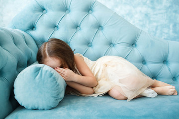 Girl hides her face in palms lying on blue couch
