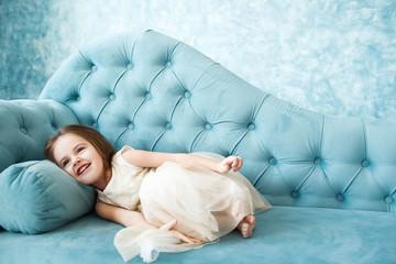 Beautiful little girl in beige dress lies on blue couch