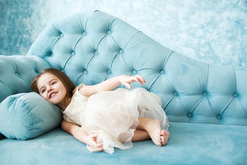 Dreamy little girl in beige dress lies on blue couch