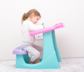 little kid girl studying desk