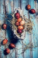 mit Zwiebelschalen gefärbte Ostereier auf türkisfarbenen Holztisch
