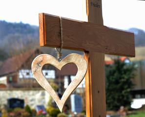 Grabkreuz aus Holz mit daran hängendem Holzherz als Erinnerung an Grab