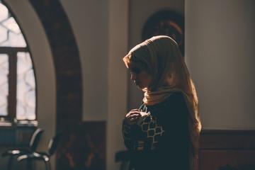 Young beautiful humble Muslim girl standing in prayer