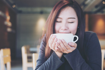 Closeup image of Asian woman smelling and drinking hot coffee with feeling good in wooden vintage cafe