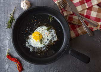 fried eggs iron frying pan rosemary spice pepper